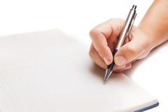 Mensenhand die in open die boek schrijven op wit wordt geïsoleerd Royalty-vrije Stock Foto's