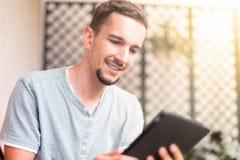Mensenhand die witte tablet in de tuin gebruiken stock foto's