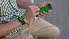Mensenhand die zijn gadgets slim horloge, smartphonezitting op het bank groene scherm met behulp van stock footage