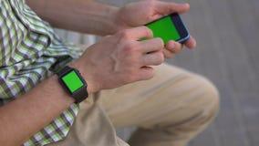 Mensenhand die zijn gadgets slim horloge, smartphonezitting op het bank groene scherm met behulp van stock video