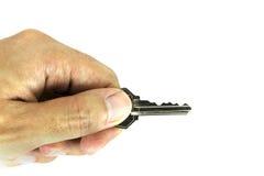 Mensenhand die zilveren die sleutel houdt op witte achtergrond wordt geïsoleerd Stock Fotografie