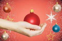 Mensenhand met de rode bal van de Kerstmisboom bij rode achtergrond Royalty-vrije Stock Foto's