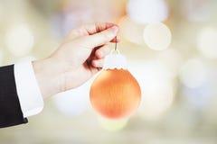 Mensenhand met het stuk speelgoed van de Kerstmisboom - oranje bal Stock Foto