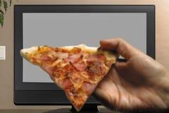 Mensenhand met pizzaplak die op TV letten Royalty-vrije Stock Afbeeldingen