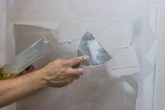 Mensenhand met troffel die een muur 2 pleisteren royalty-vrije stock afbeeldingen