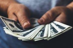 Mensenhanden die de dollarbankbiljetten houden die van de V.S. uit door ventilator worden uitgespreid, die het succesconcept make Stock Afbeelding