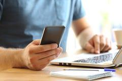 Mensenhanden die een slimme telefoon op een Desktop met behulp van Stock Fotografie