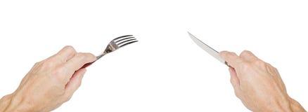 Mensenhanden die een zilveren vork en een mes houden Stock Afbeeldingen