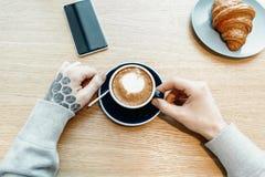 Mensenhanden die kop van koffie houden Het croissant en de mobiele telefoon zijn op achtergrond royalty-vrije stock fotografie