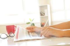 Mensenhanden die krant lezen Stock Afbeelding