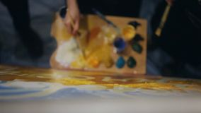 Mensenhanden die samen met penselen op het witte canvas schilderen stock video