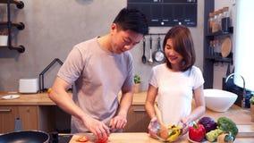 Mensenhanden die tomaat in de keuken snijden Het mooie gelukkige Aziatische paar kookt in de keuken stock videobeelden