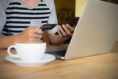 Mensenhanden gebruikend smartphonelaptop en houdend creditcard met s royalty-vrije stock foto