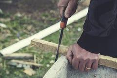 Mensenhandzagen met hout stock afbeelding