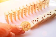 Mensenholding bitcoin en vernietigend de rij van domino's Stock Afbeeldingen