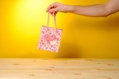 Mensenholding huidig in roze het winkelen zak stock foto's