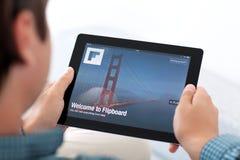 Mensenholding iPad met app Flipboard op het scherm Stock Afbeelding
