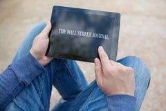 Mensenholding ipad met Wall Street Journal op het scherm Stock Fotografie