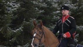 Mensenhorseback die een groot bruin paard in mooi sneeuw de winterlandschap berijden Het mannelijke ruiter cantering met grote el stock video
