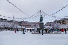 Mensenijs die bij het Kungsträdgården-park in het midden van de stad op een de winterdag schaatsen stock foto's