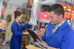 Menseninspecteur die inventaris in pakhuis doen royalty-vrije stock afbeeldingen