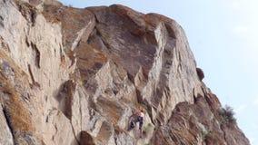 Mensenklimmer die en de rots wandelen beklimmen stock videobeelden