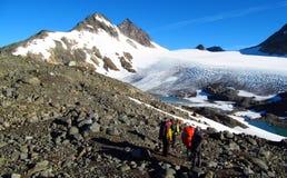 Mensenklimmers, die aan de top, de rotsachtige bergpieken en de gletsjer in Noorwegen beklimmen Stock Foto