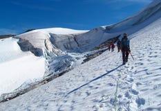 Mensenklimmers, die sneeuwtop, rotsachtige bergpieken en gletsjer in Noorwegen beklimmen Stock Fotografie