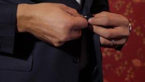 Mensenknoop omhoog zijn knopen op zijn jasje, close-up de bedrijfsmens in de ochtend zet op het werk stock videobeelden