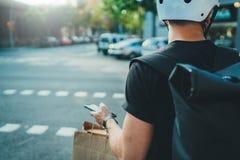 Mensenkoerier die een kaart app op mobiele telefoon gebruiken om het afleveradres in de stad te vinden De leveringsvoedsel van de stock foto's