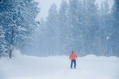 Mensenlanglaufski in oranje jasje, zwarte broeken in werking die wordt gesteld die De dag van de de wintersneeuw stock fotografie