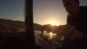 Mensenlaptop de zakenman freelancer silhouetteert mensenlaptop die achter het zitten bij strand het freelancing in de zon werken royalty-vrije stock afbeelding