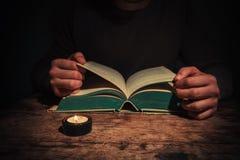 Mensenlezing door kaarslicht royalty-vrije stock afbeeldingen