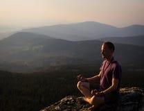 Mensenmeditatie op een rots Stock Fotografie