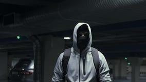 Mensenmisdadiger in balaclava en de kap die de camera in ondergronds parkeren, langzame mo bekijken stock videobeelden