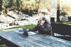 Mensenondernemer met laptop die op de telefoon in bos spreken stock foto
