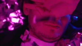 Mensenontwaken onder confettien, die slecht na de partij van de nachtclub, kater voelen stock footage