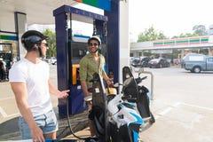 Mensenpaar op de Motorfiets van de Benzinestationbrandstof, het Gelukkige het Glimlachen Kerels Reizen royalty-vrije stock foto's