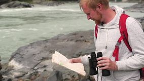 Mensenreizen in de bergen de toerist met kaart en verrekijkers zoekt de manier in de bergen jonge gekregen toerist stock video