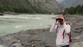 Mensenreizen in de bergen de toerist met kaart en verrekijkers zoekt de manier in de bergen jonge gekregen toerist stock videobeelden