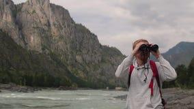 Mensenreizen in de bergen de toerist met kaart en verrekijkers zoekt de manier in de bergen jonge gekregen toerist stock footage