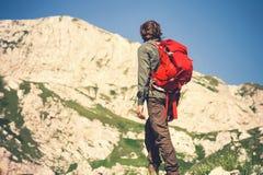 Mensenreiziger die met rode rugzak het concept van de Reislevensstijl beklimmen Stock Foto's