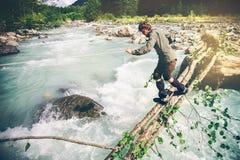 Mensenreiziger die over rivier op hout kruisen openlucht Royalty-vrije Stock Afbeeldingen
