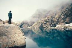Mensenreiziger die zich alleen op het meer van de steenklip en nevelige bergen op achtergrond bevinden Royalty-vrije Stock Foto's