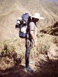 Mensenreiziger met hoed en rugzak de Reislevensstijl van wandelingsbergen stock foto