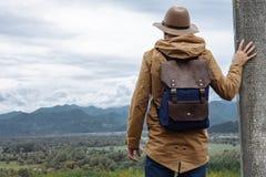 Mensenreiziger met hoed en rugzak die van de natuurlijke rand genieten Stock Afbeelding