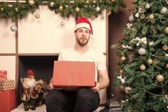 Mensensanta met verraste gezichtsgreep huidig bij Kerstmisboom stock afbeeldingen