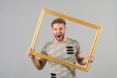 Mensenschreeuw met omlijsting op grijze achtergrond Boze macho met houten de fotokader van de baardgreep Kerel met leeg kader Cre Stock Foto's