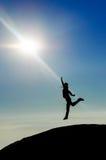 Mensensilhouet die bereikend de zon springen Royalty-vrije Stock Fotografie