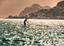 Mensensilhouet die met peddelraad surfen Stock Foto's